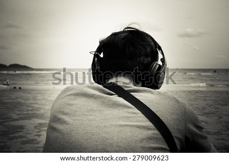 young man listening music on the beach (black and white)