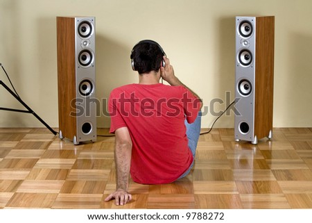 Young man listening music with earphones and modern loudspeakers