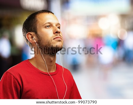 young man listening to music against a city background