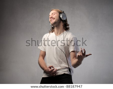 Young man listening to music and playing an air guitar