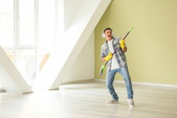 Young man listening to music and singing while cleaning his flat