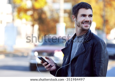 Young man listening to music and walking along the street #351984497