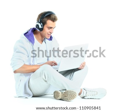 Young man listening to music from his laptop