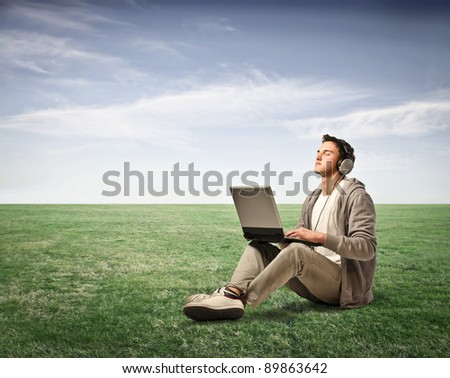 Young man listening to music from his laptop on a green meadow