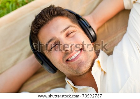 Young man listening to music in the park - stock photo