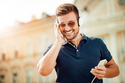 Young man listening to music on a smart phone in the city