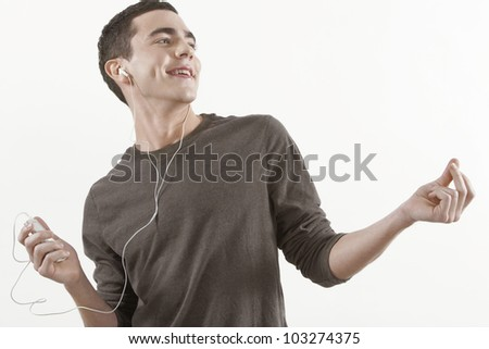 Young man listening to music through earphones and clicking his fingers to the rhythm, on a white background.