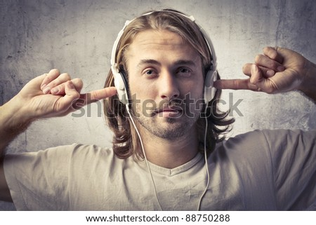 Young man listening to music through headphones