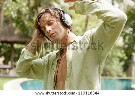 Young man listening to music with headphones while standing next to a swimming pool in a tropical garden.