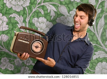 Young Man Listening To Vintage Radio On Wallpaper