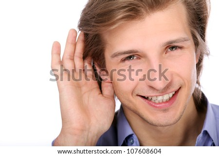 Young man listening with hand on ear over white background
