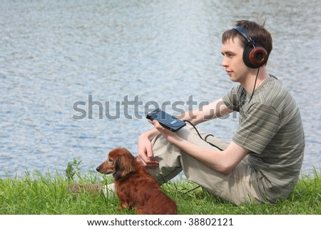 Young man listens music in headphones sits on grass with his dachshund ashore