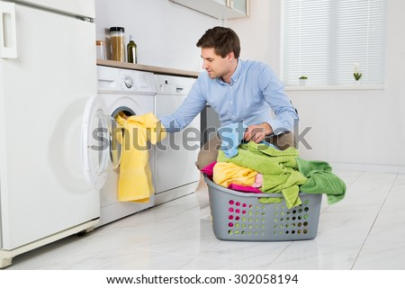 Young Man Loading Clothes Into Washing Machine In Kitchen #302058194