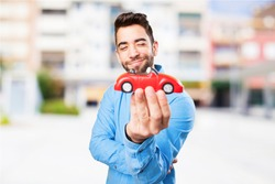 young man looking a red car