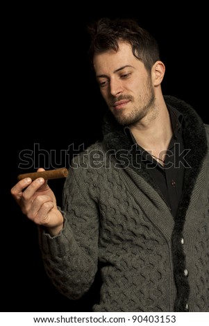 Young man looking at a cigar, isolated over black background