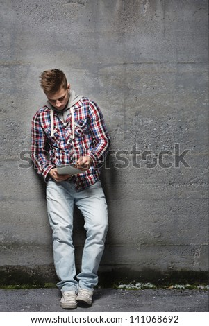 Young man looking at a tablet screen, standing and leaning against a concrete wall outside