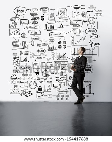 young man looking at drawing business concept on wall