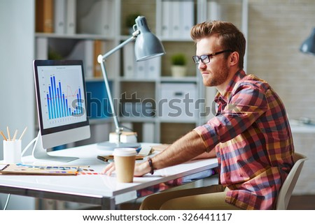 Young man looking at financial chart reflecting changes in market development