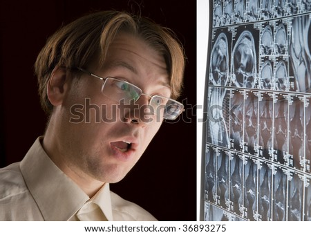 Young man looking at MRI film in horror