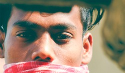 Young man looking at the camera. Doubt,hopeless,positive,proud,brave,glad facial expressions. Detail shot of boys face with eyes. Copyspace.Attractive boy with a gamcha in face as a mask