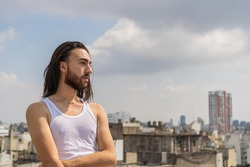 young man looking at the city from an urban rooftop, with the city and the sky in the background. long-haired, bearded man wearing a white sleeveless t-shirt. muscle shirt.