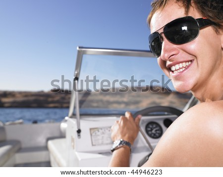 Young man looking back towards camera while smiling and driving boat. Horizontal shot. - stock photo
