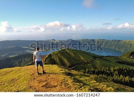 Young man looking into crater of Lagoa Azul and Lagoa Verde (Blue Lake and Green Lake) in Sete Cidades on Sao Miguel, Azore Islands, Portugal. The Azores are known for beautiful nature and landscape. Foto stock ©