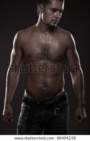 young man looking manly covered with water drops