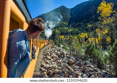 Young man looking out of train window on the historic steam engine train travelling from Durango to Silverton along the Animas River in Colorado, USA.