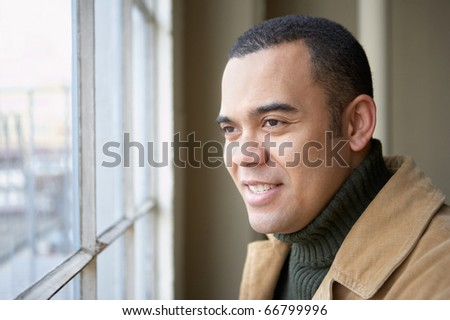 Young man looking out window