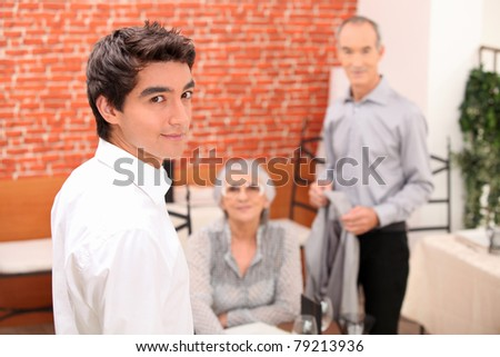 Young man looking over his shoulder as a senior couple make to leave a restaurant