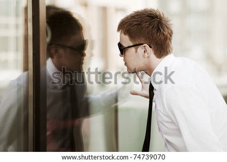 Young man looking through a window