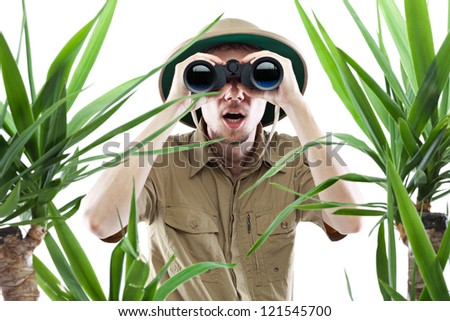 Young man looking through binoculars with an amazed expression, palm trees on foreground out of focus, isolated on white #121545700