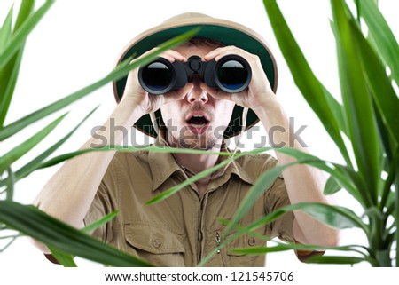 Young man looking through binoculars with an amazed expression, palm trees on foreground out of focus, isolated on white #121545706