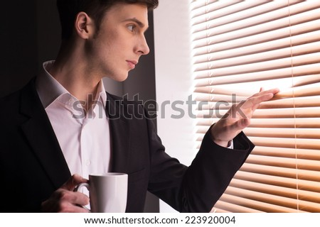 young man looking through window blinds. Handsome business guy peeking through blinds and drinking