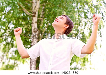 young man looking to the sky, holding his hands up, the expectation of success