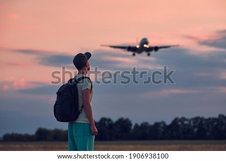 Young man looking up at flying airplane against moody sky during dusk. Themes nostalgia for travel and aviation. Foto stock ©