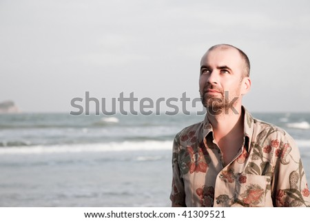 Young man looking up on the beach
