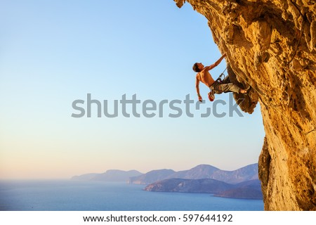 Young man looking up while climbing challenging route on cliff #597644192