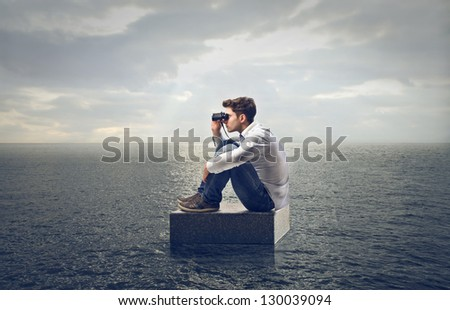 young man looking with binoculars
