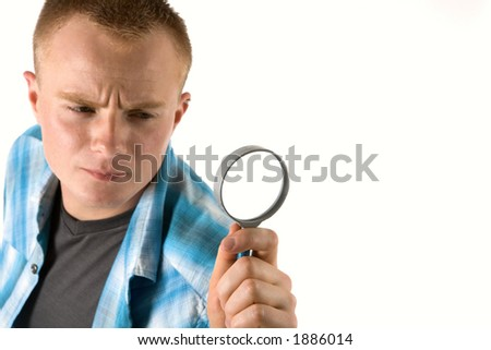 young man looks through a magnifying glass (focus on glass)