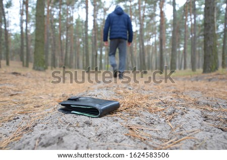 Young man loses his purse with euro money bills on Russian autumn fir wood path. Carelessness and losing wallet concept