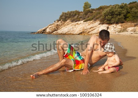 Young man lying at the beach and playing with 9 months old baby
