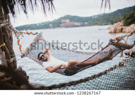 Young man lying in a hammock by the ocean. A handsome guy is resting in a hammock against the backdrop of the mountains by the sea.