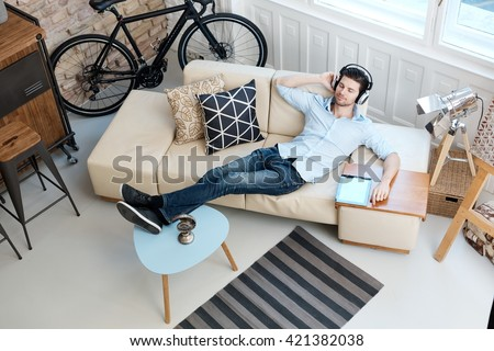 Young man lying on sofa at home, listening to music through headphones eyes closed.