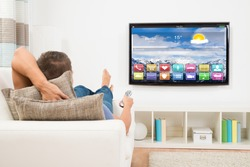 Young Man Lying On Sofa Using Remote Control In Front Of Television