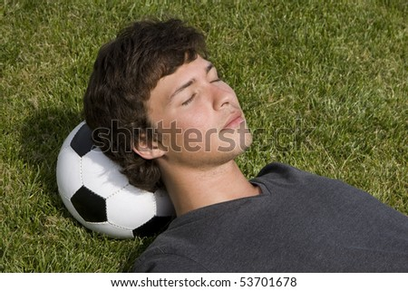 Young man lying on the grass over a soccer ball