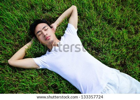young man lying on the green grass, Healty lifestyle.
