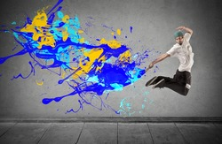 young man makes a big jump while painting the wall