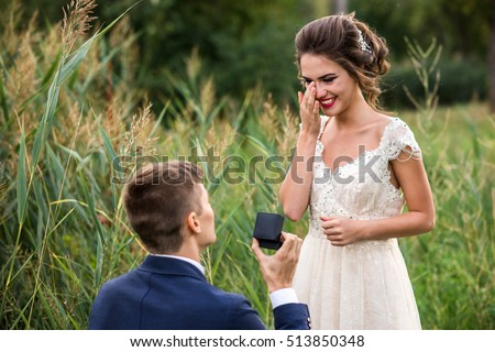 Young man makes a proposal to get married, the bride is crying from happiness Stock photo ©
